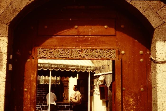 De toegangspoort tot het al-Gasmi-hotel in Sana'a. De calligrafie boven de poort is lastig te lezen omdat de letters in elkaar gevlochten zijn. Het eerste woord, dat helemaal rechts staat, is zeer waarschijnlijk 'Diwaan'. Dit woord komt in de koran niet voor, dus de tekst is geen koranvers. Het eerste woord staat rechts, omdat Arabisch van rechts naar links geschreven wordt. In vrijwel alle Arabische calligrafiën zijn de letters kunstig in elkaar gevlochten, om op zo weinig mogelijk ruimte zoveel mogelijk te kunnen schrijven.